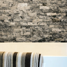 Silver Splitface Travertine Ledgestone accent wall installed next to a freestanding tub