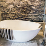 Silver Splitface Travertine Ledgestone installed next to a freestanding tub